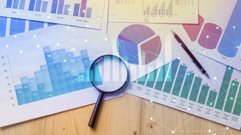 magnifying glass sitting on printouts of charts