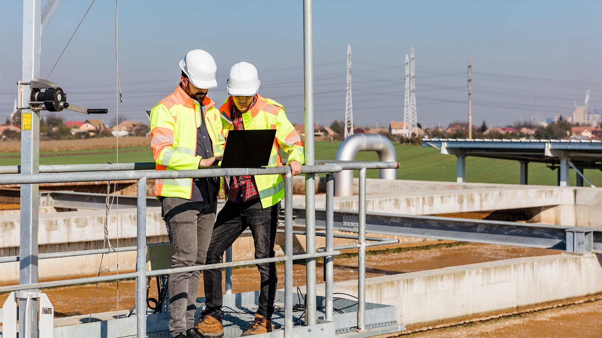 Two men wearing white hard hats and yellow and orange safety jackets standing outside at a water plant entering information into a laptop.