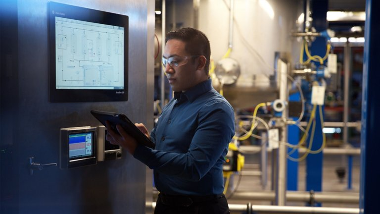 Male employee entering information into a tablet from what he is viewing on a panel on a system in a plant.