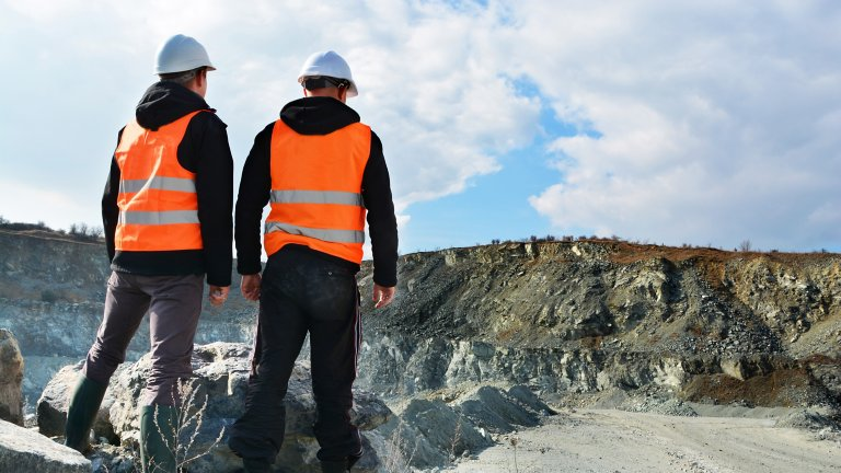 Two men wearing white hard hats and orange vests in a mining location