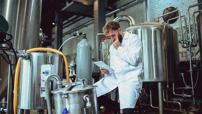 Medewerker bij een brouwerij die een tablet raadpleegt