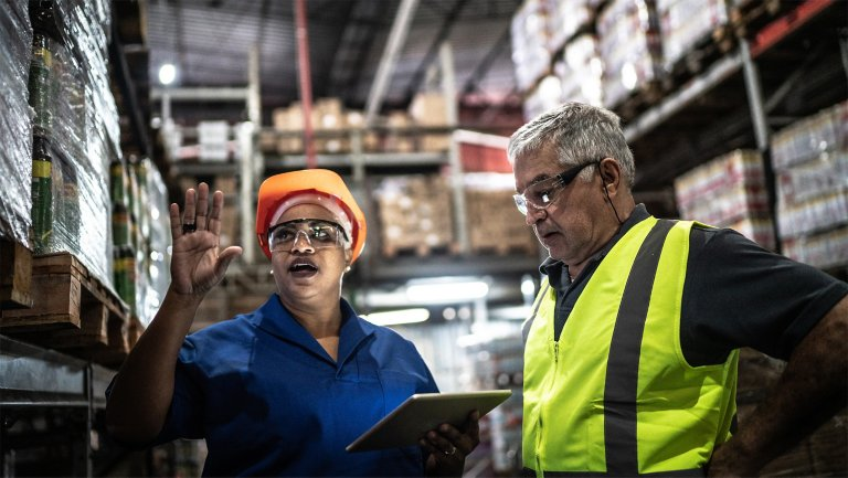 Two employees in the stock area of a plant discussing information they are reviewing on a tablet