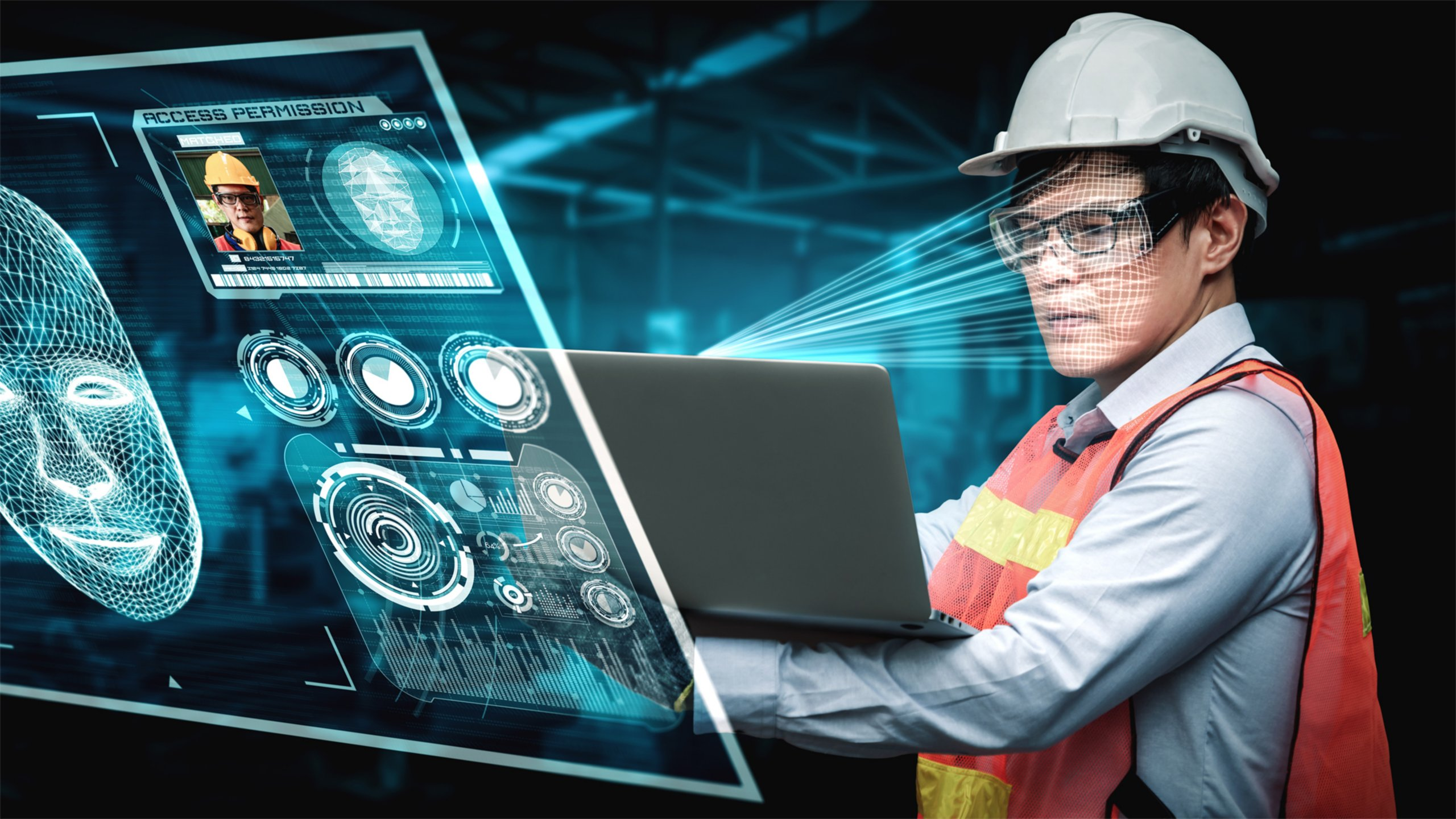 Man in a manufacturing setting, wearing a hard hat and orange safety vest while looking at a laptop. The information he is seeing is being shown in front of him.