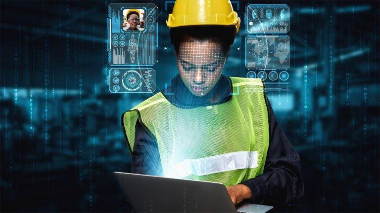 Woman wearing a yellow hard had and yellow safety vest looking at a laptop getting information. The information she is seeing is being shown in the background.