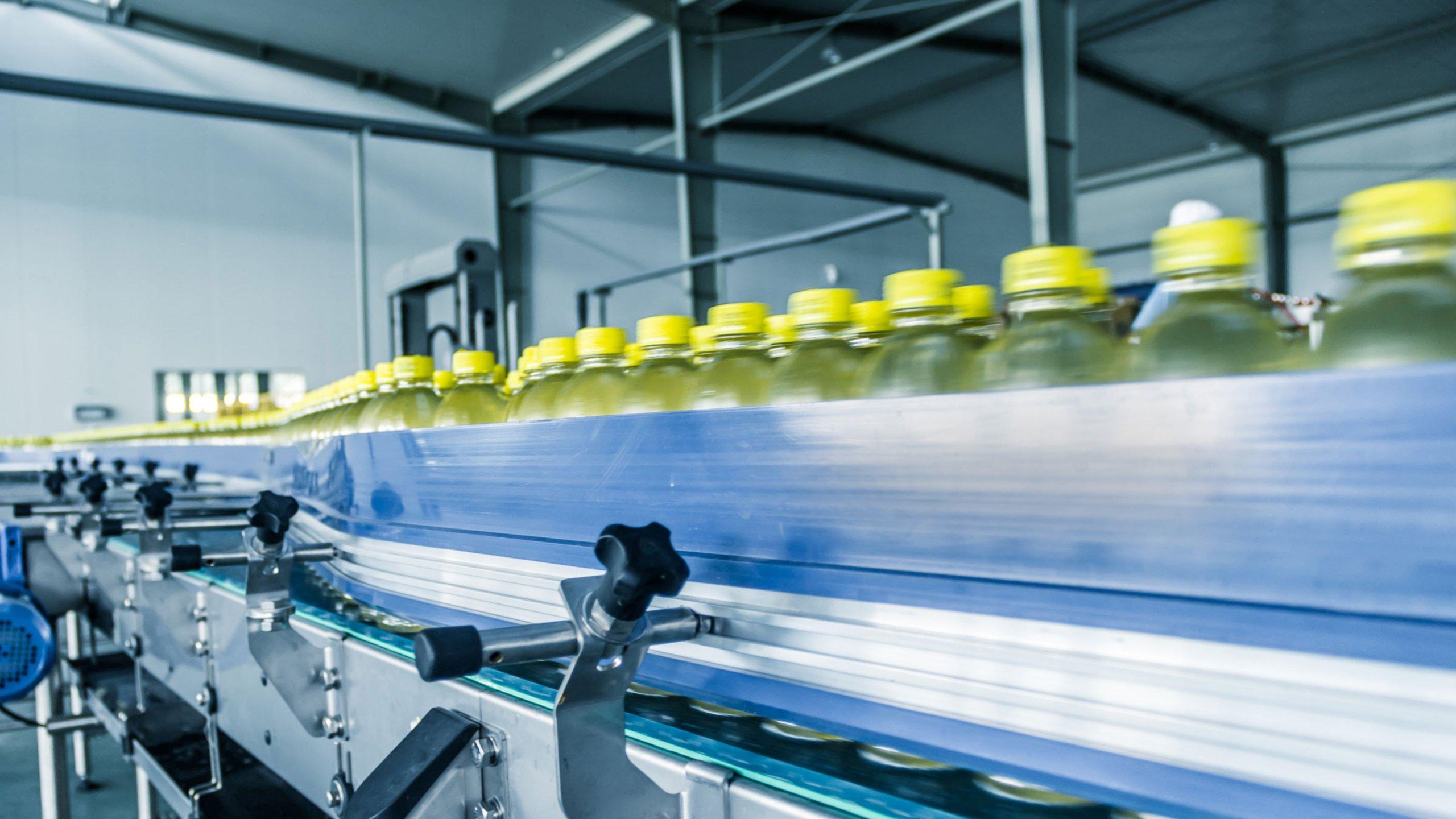 Productielijn met flessen met gele doppen die over een lopende band worden getransporteerd