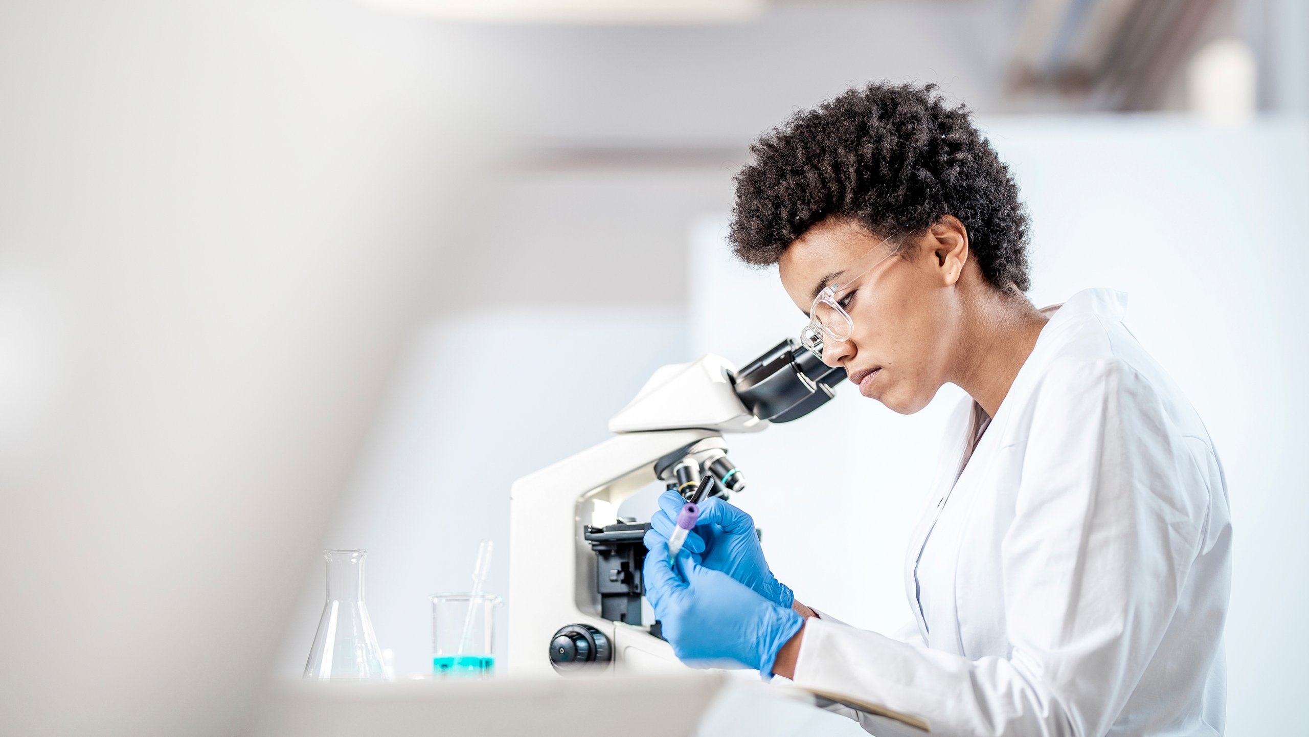 Female lab technician writing information on a test tube with a marker after viewing results in a microscope