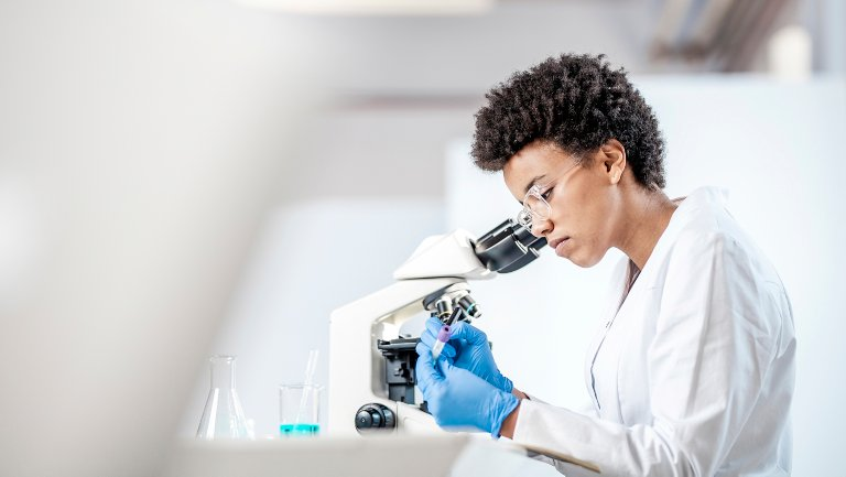Biopharmaceutical employee observing results in a microscope