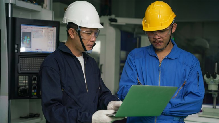 Two men in a manufacturing setting, wearing hard hats, safety glasses, and manufacturing uniforms looking at a laptop together.