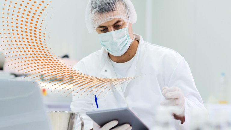 Biotech lab technician wearing PPE and viewing information on a tablet