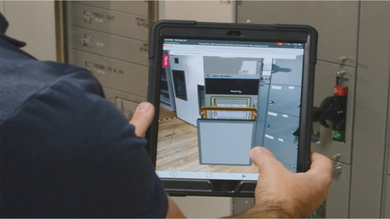 A worker in a manufacturing environment is using a tablet to access an augmented reality library of work instructions that provides detailed images of a maintenance task being done on a PowerFlex AC drive so he can follow along and easily accomplish the task.