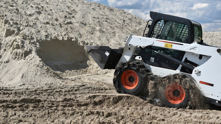 Bobcat equipment used to scoop sand from pile