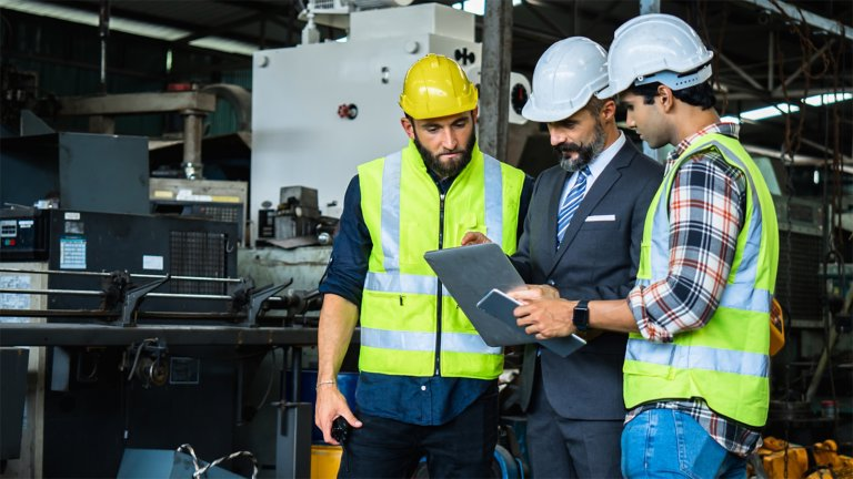 Three men in a manufacturing setting wearing hard hats looking at a tablet. The first man and the third man are wearing safety vests. The man in the middle is holding the tablet and wearing a business suit with a tie.