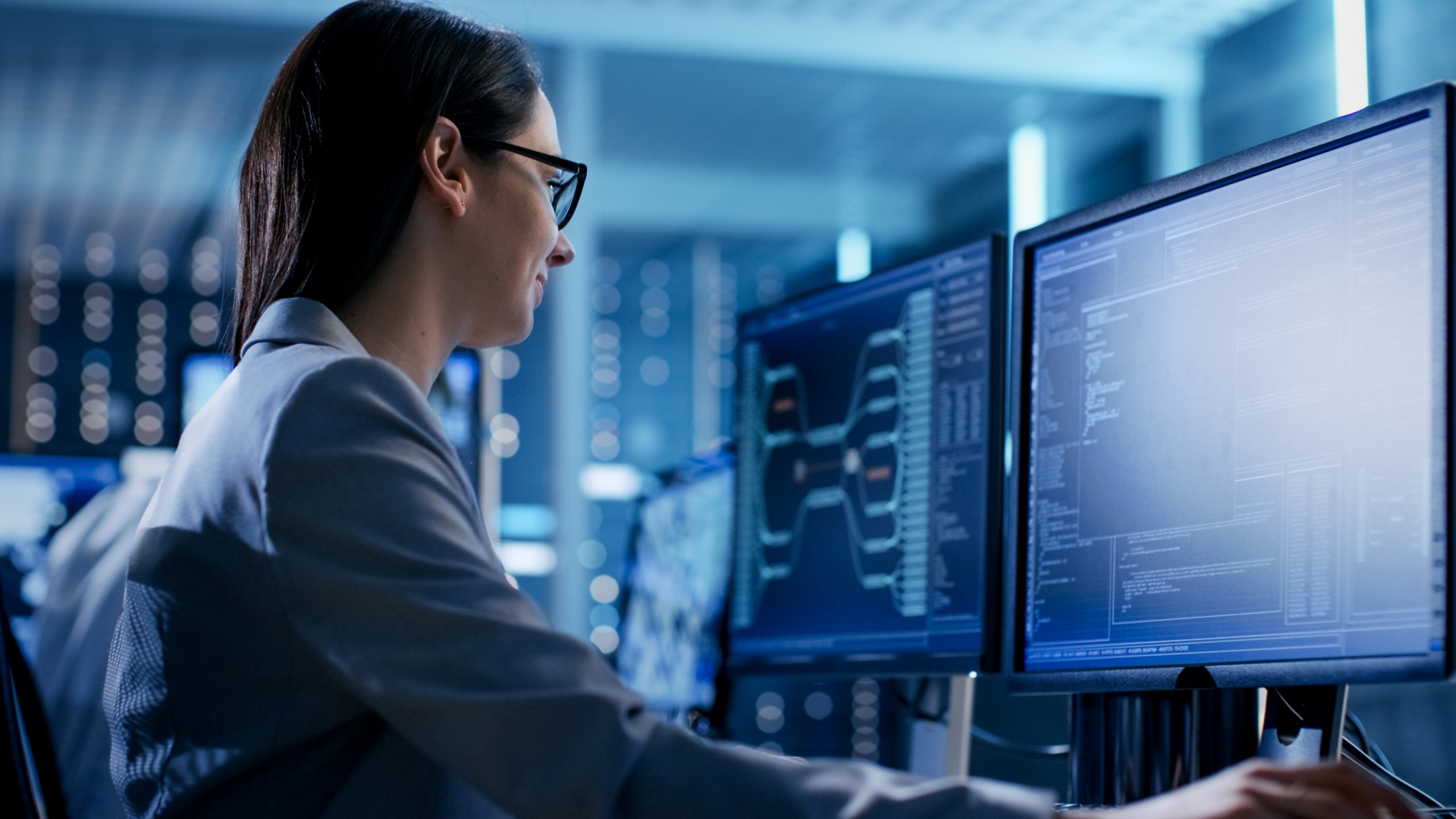 Female employee with glasses sitting beside a coworker in a technical area viewing software on her monitor