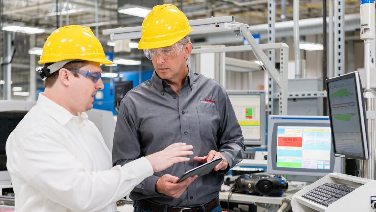 Two workers collaborate on a tablet device in a plant floor environment. One man is wearing a Rockwell Automation shirt
