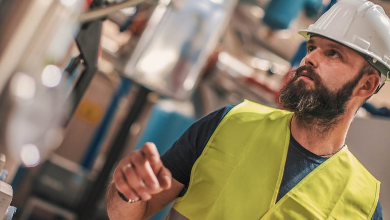 Male employee with a beard and mustache wearing a hard hat and a yellow vest in a factory looking serious