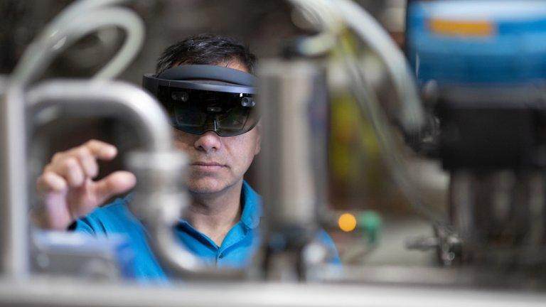 man wearing virtual reality headset manipulating hardware