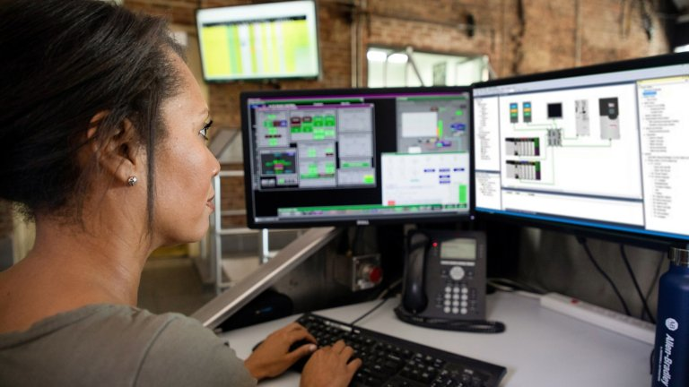 Side profile of a female employee sitting at her desk typing on her keyboard and viewing two moitors displaying a software application