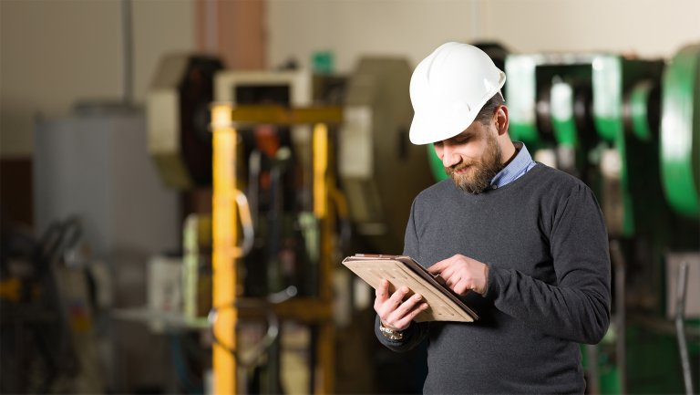 Man holding tablet device and looking at equipment on production floor