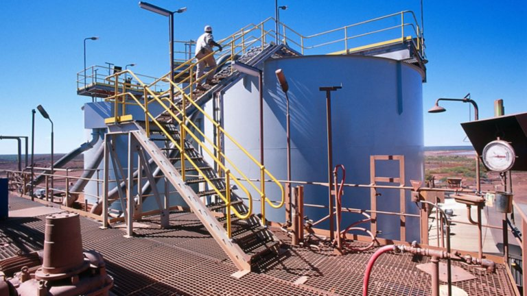 Employee walking up stairs to the top of a containment tank