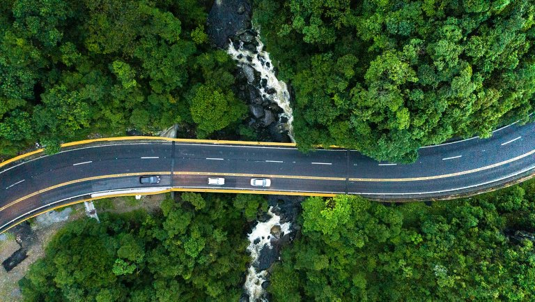 Remote aerial view of winding road with moving vehicles