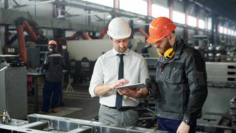 Two engineers wearing hard hats using a tablet on industrial plant floor