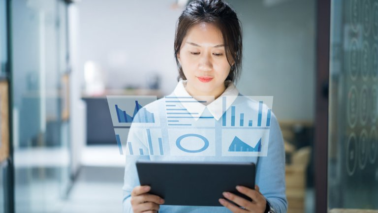 Business person looking at a tablet device, illustration depicts charts and graphs projecting off the device screen
