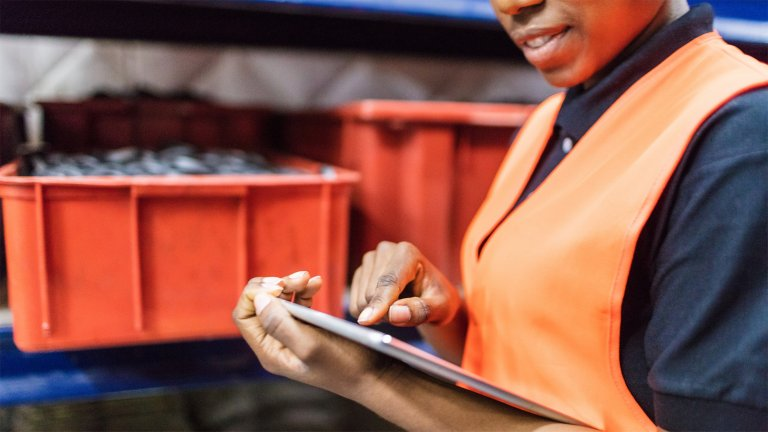 Employee viewing her tablet beside a conveyor with parts in bins