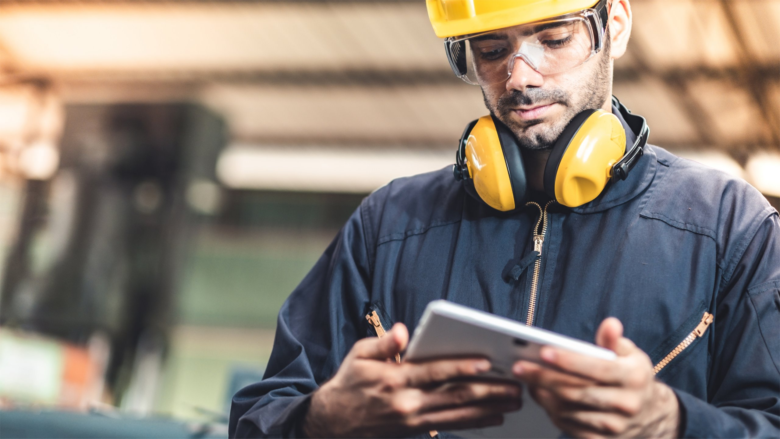 Employee in factory viewing information on his tablet