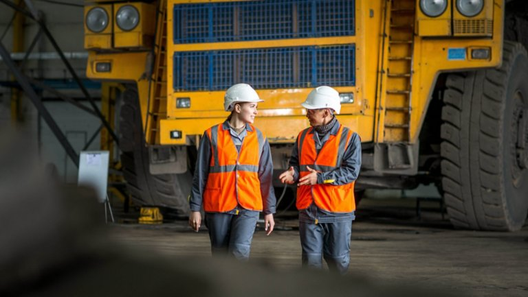 Two mining employees discussing mining vehicle performance at a mining site in front of a dump truck