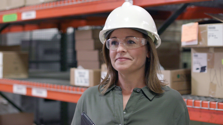 Femme avec un casque dans le magasin de l'usine.