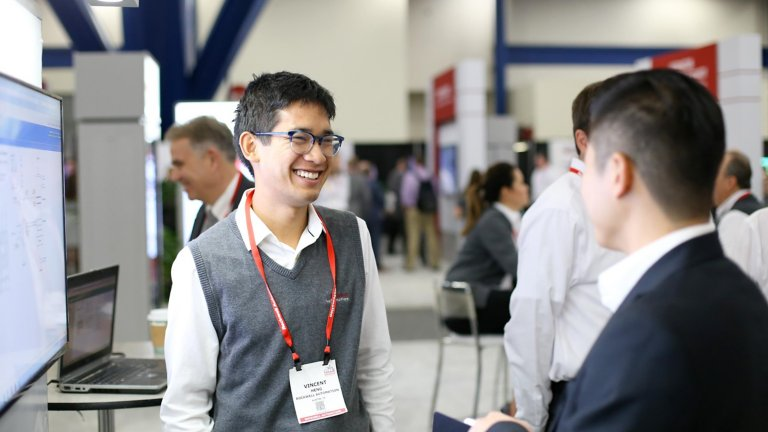 two men standing in booth area discussing digital engineering