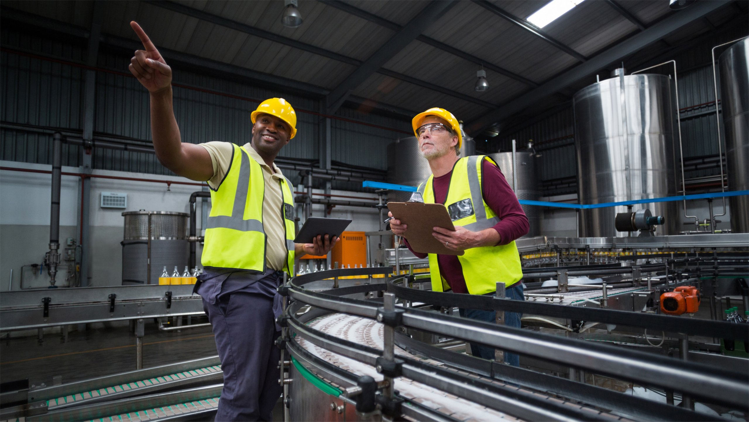 Two plant workers stand near manufacturing line sharing information on tablet and clipboard