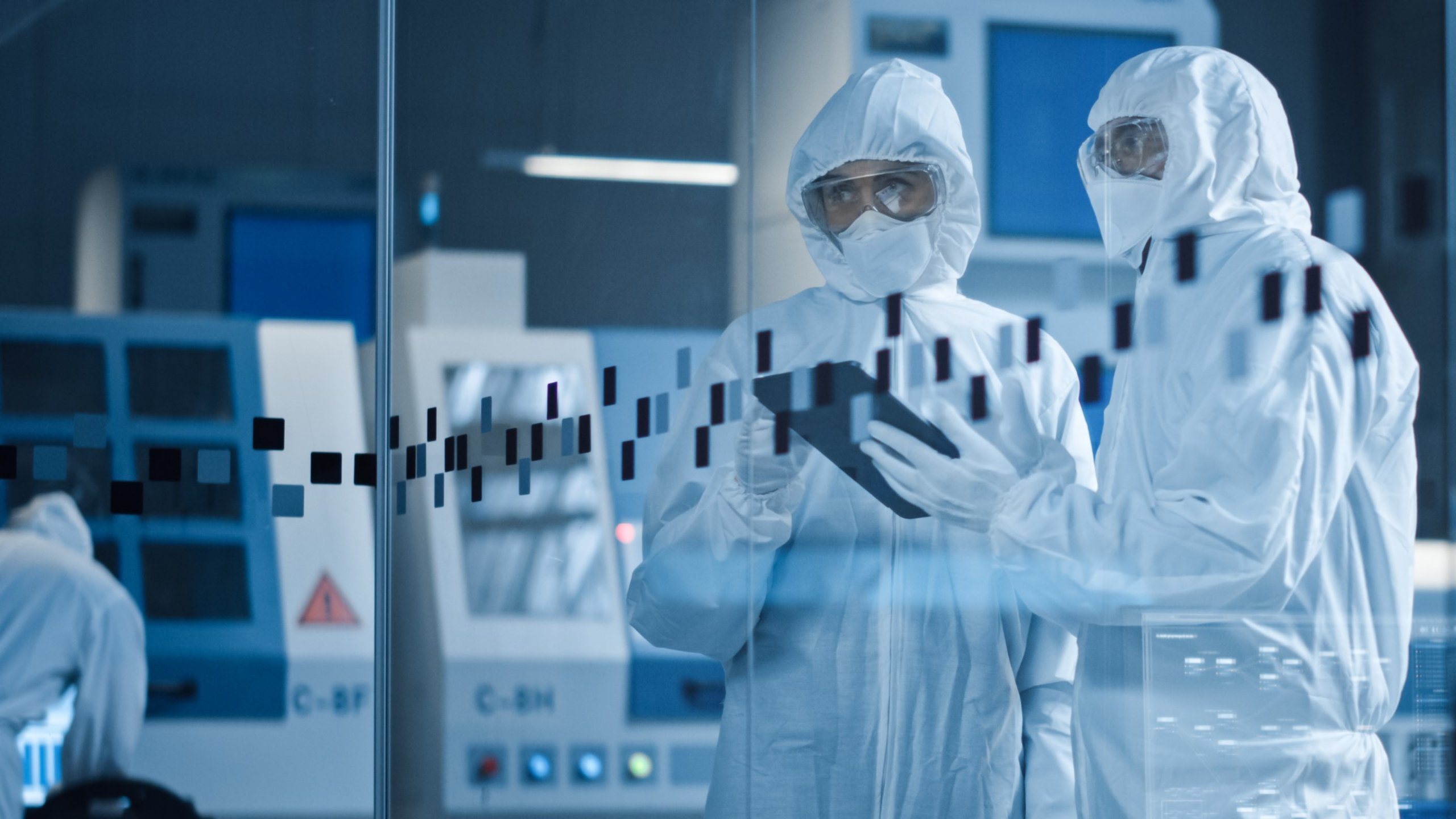 Two Life Sciences professionals in coveralls and safety glasses review analytics on a tablet while looking in on the production process at their organization's facility.