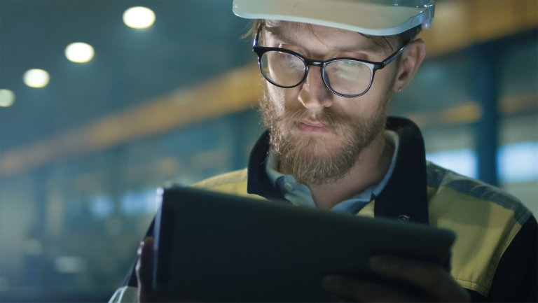 Employee in a factory looking at data on his tablet