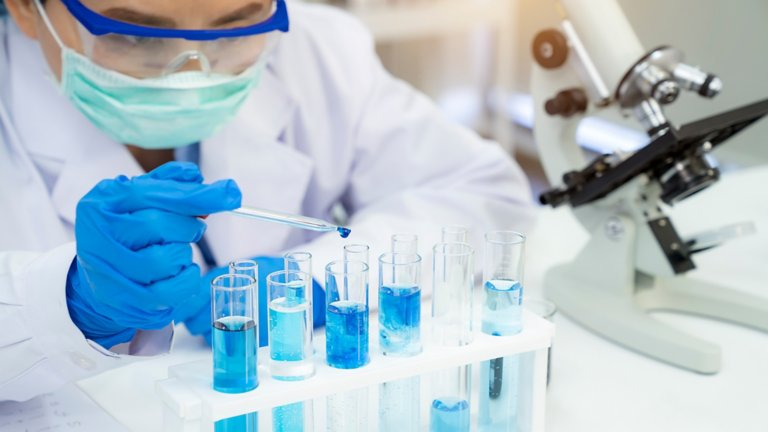 Man wearing protective gear in a lab dropping blue liquid in test tubes next to a microscope.