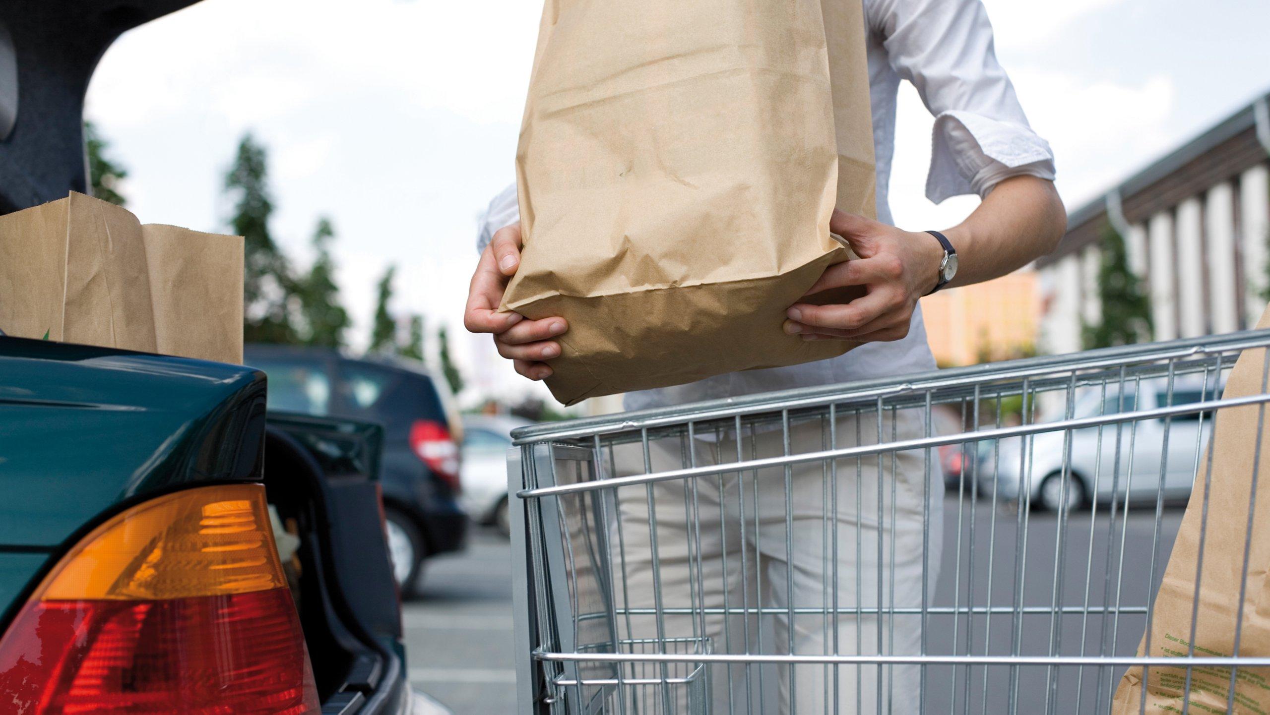 Donna che carica le borse della spesa nel suo veicolo da un carrello