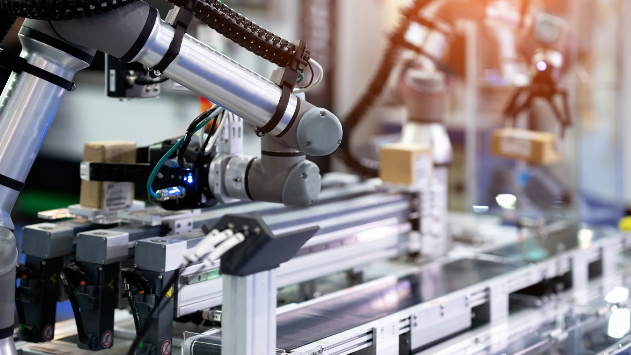 A collaborative robot placing boxes on a conveyor for labels to be scanned while another picks product that has completed the process and is carrying it to the next operation station.