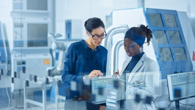 Two women dressed in business attire are in a manufacturing setting looking at a tablet.