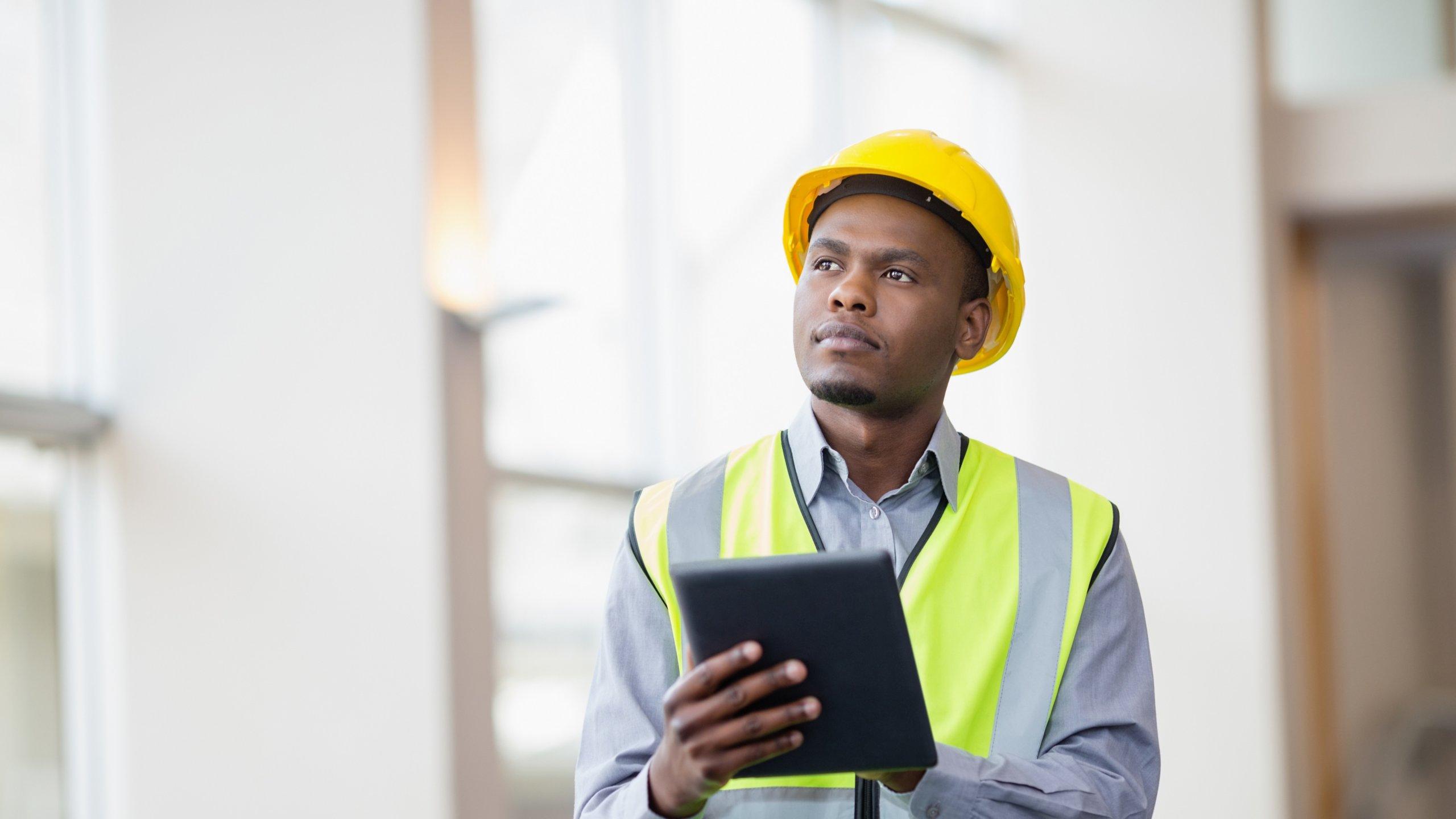 Maintenance engineer wearing yellow hard hat checking preventive maintenance data outside factory.