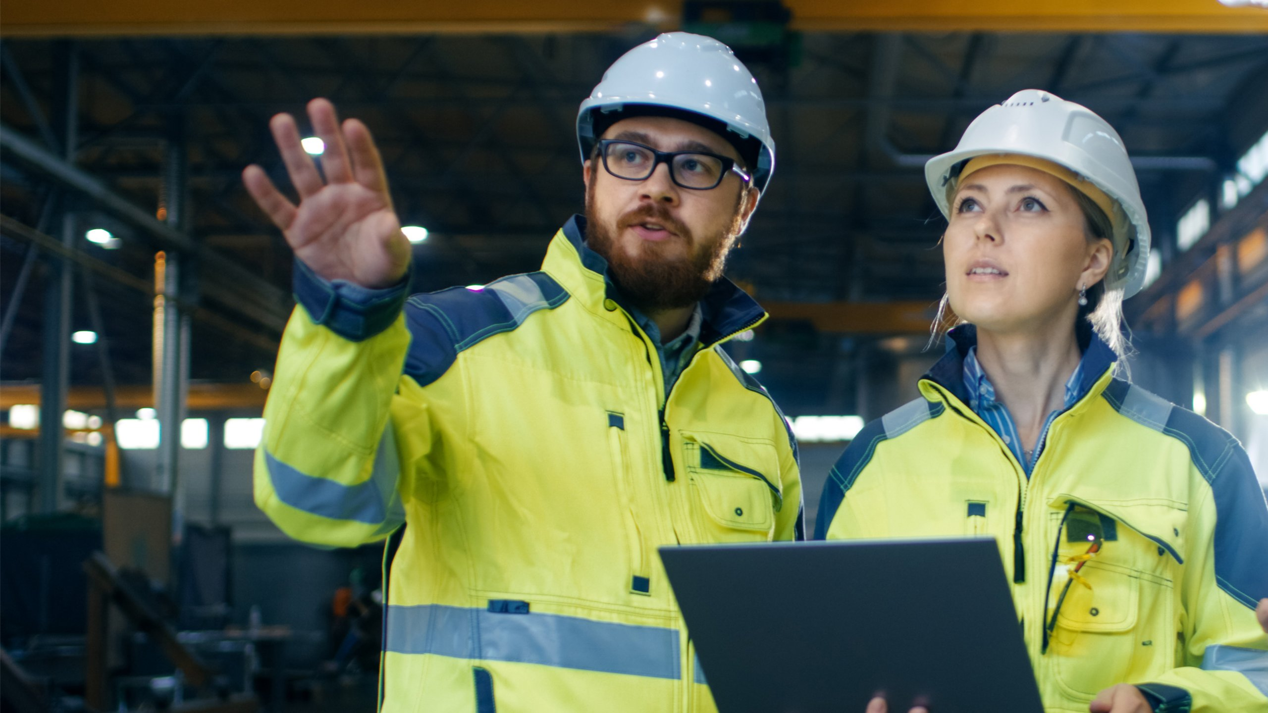 Man on left, woman on right in a manufacturing environment having a discussion while looking at a tablet. Both are wearing yellow safety coats and white hard hats.