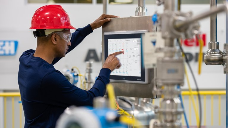 Male Rockwell Automation employee wearing a red hard hat entering information on a touch screen of a monitor in the factory
