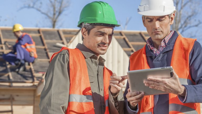 Two workers wearing hard hats and orange safety vests viewing information on a tablet