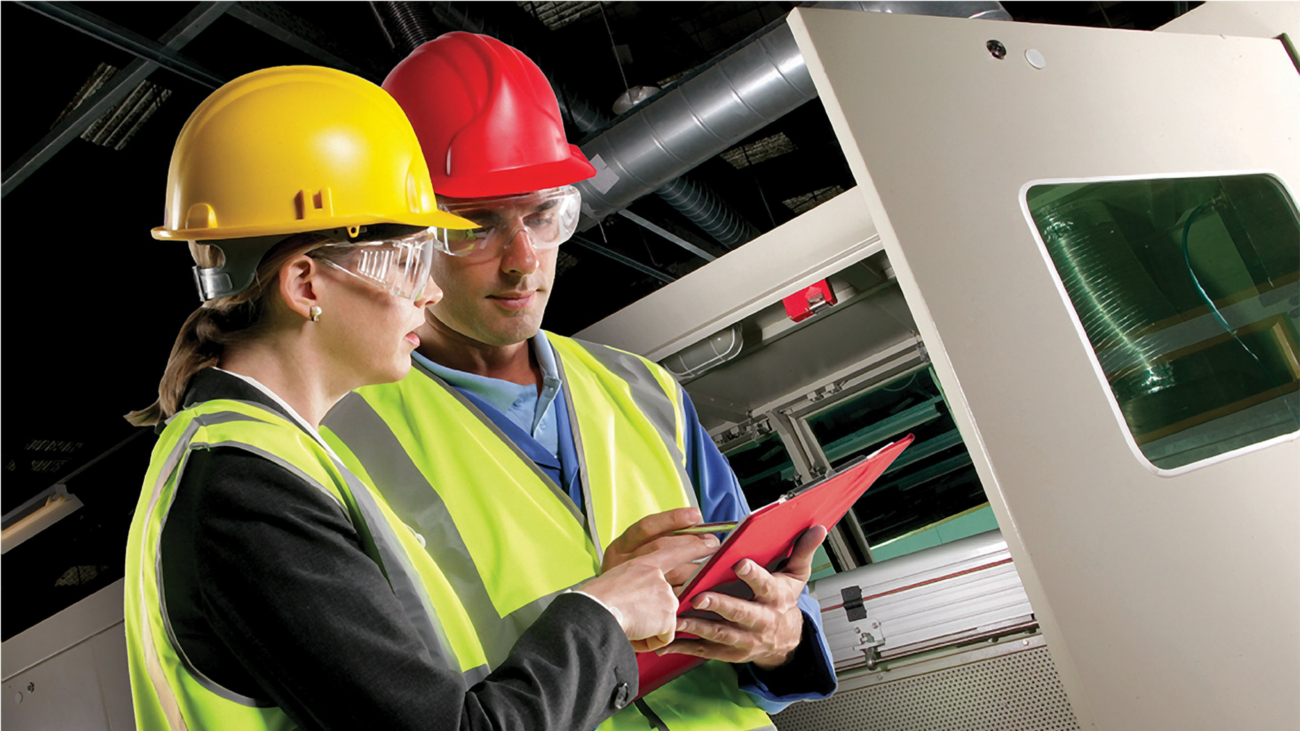 Female and male dressed in safety glasses, yellow reflective safety vests and yellow and red hard hats, looking at a red clipboard while in discussion in an industrial safety setting