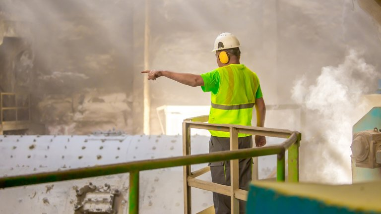 Worker in a cement plant pointing to provide instructions while standing above machinery