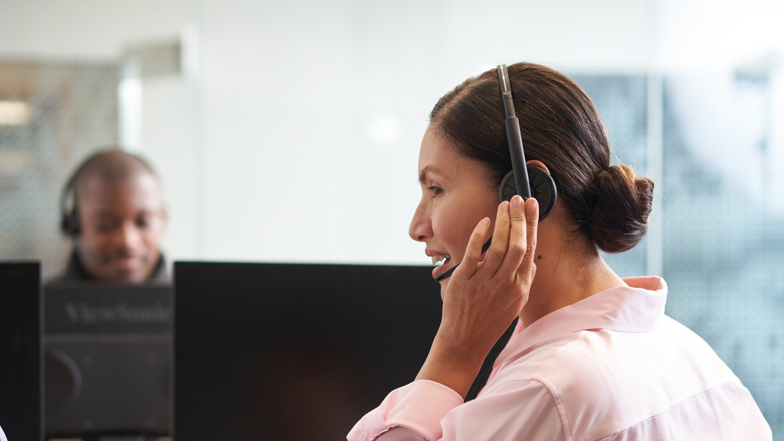 customer care representative speaking into a headset while sitting in front of a computer