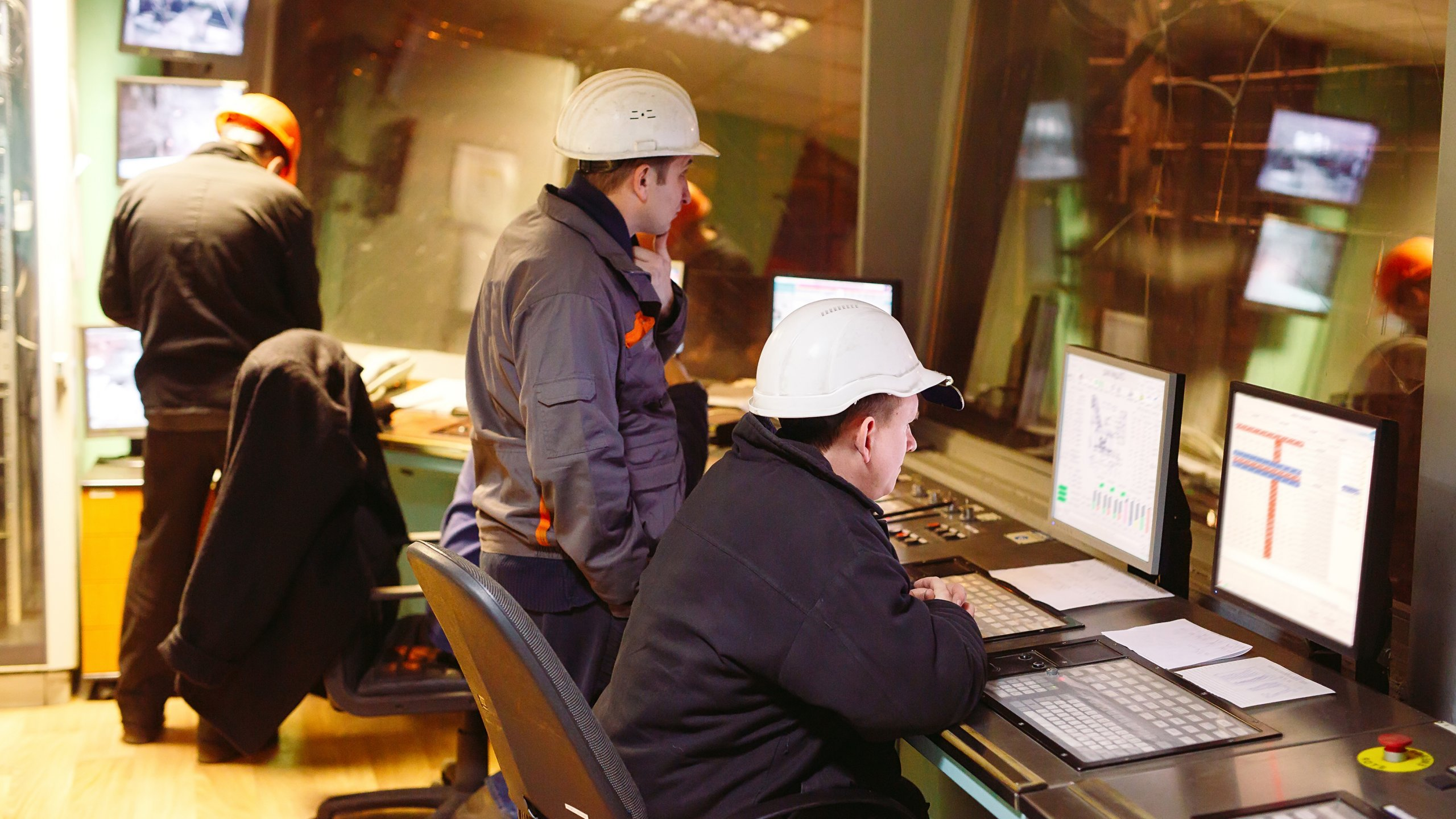 Employees at desk wearing hard hats viewing the plant floor and software on their laptops
