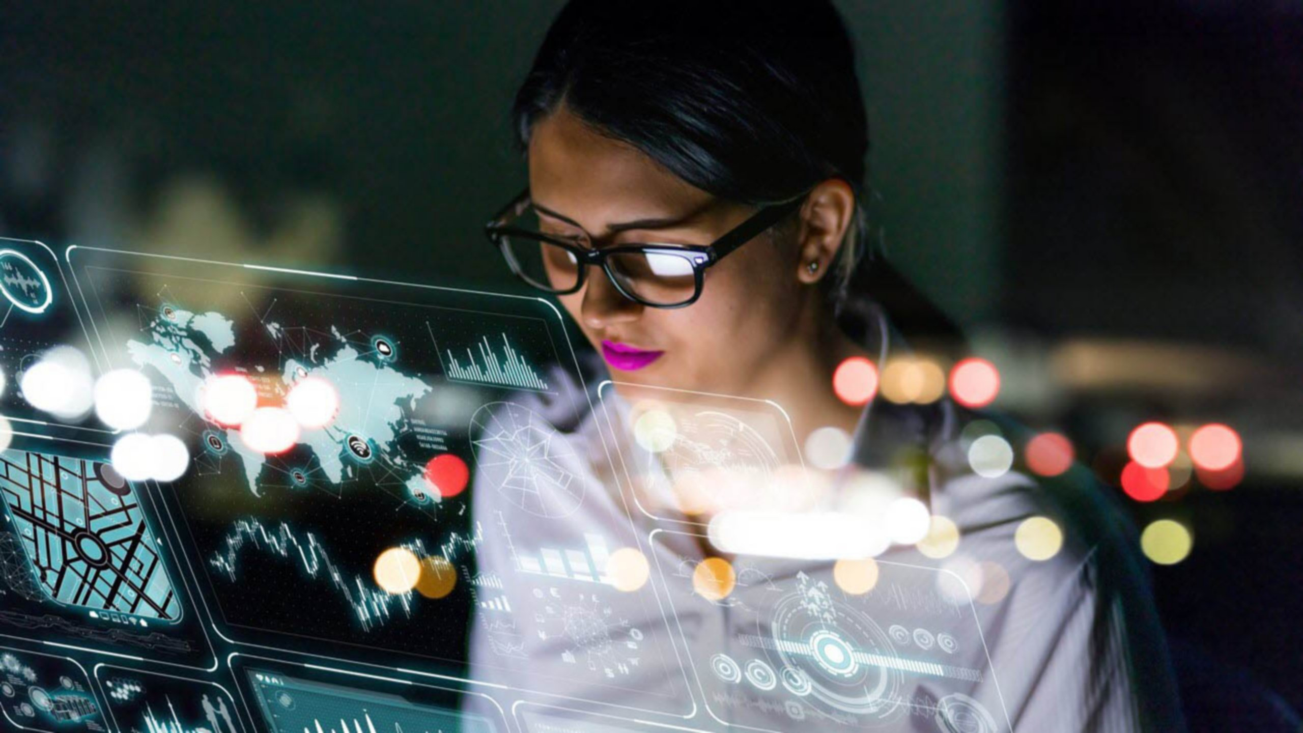 Female engineer wearing glasses at her desk viewing software on her laptop