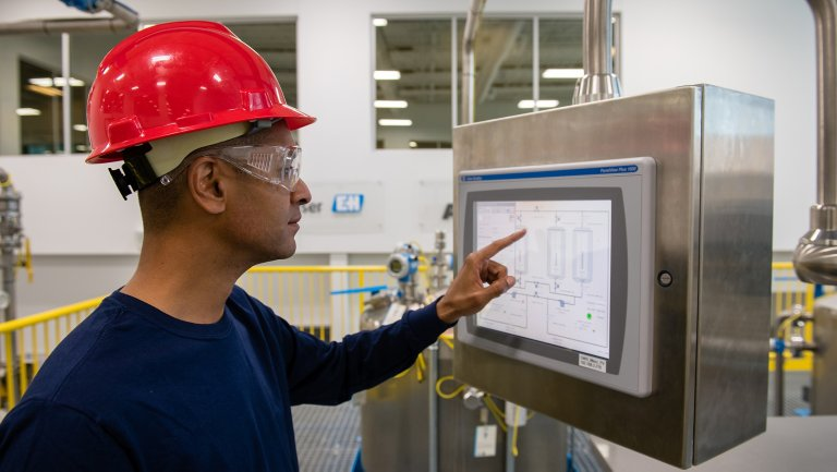 Plant floor employee using touch panel screen to retrieve information.