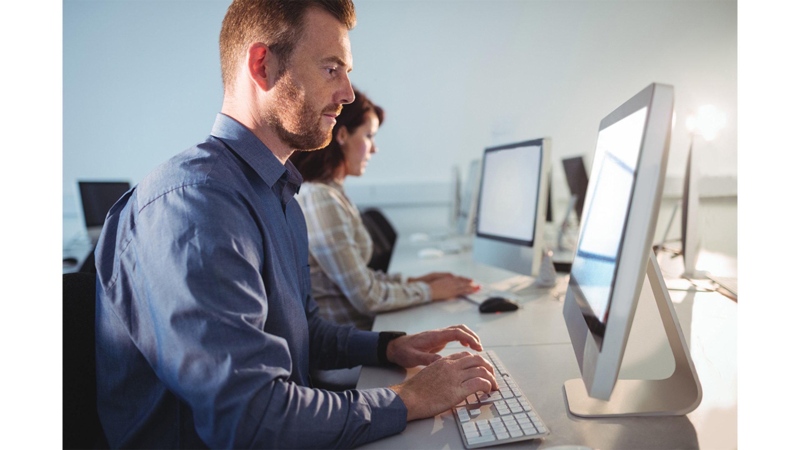 Man and woman sitting in front of computers engaged in on-line training