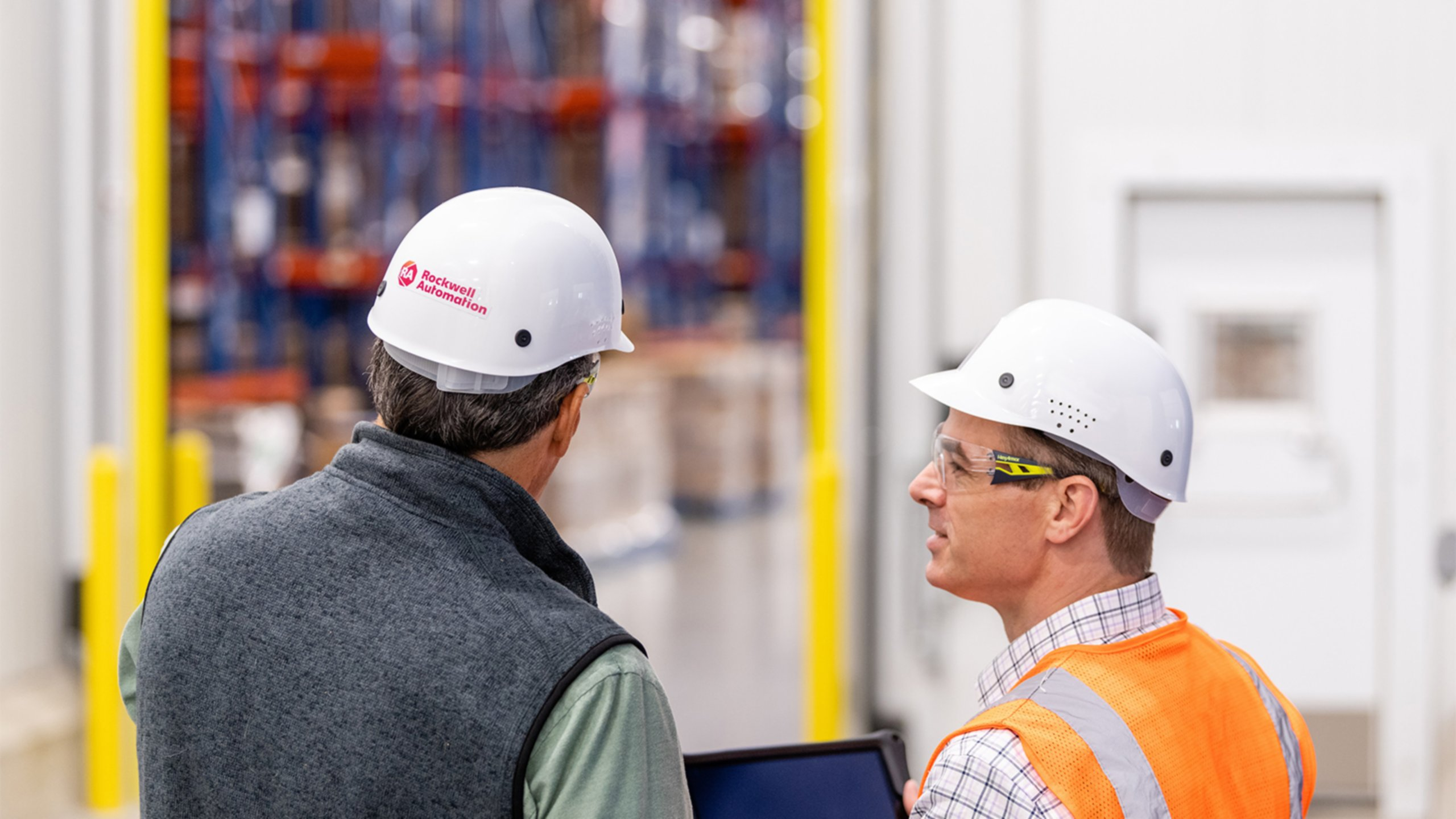 Rockwell Automation consultant in hard hat looks at tablet with male client in orange vest